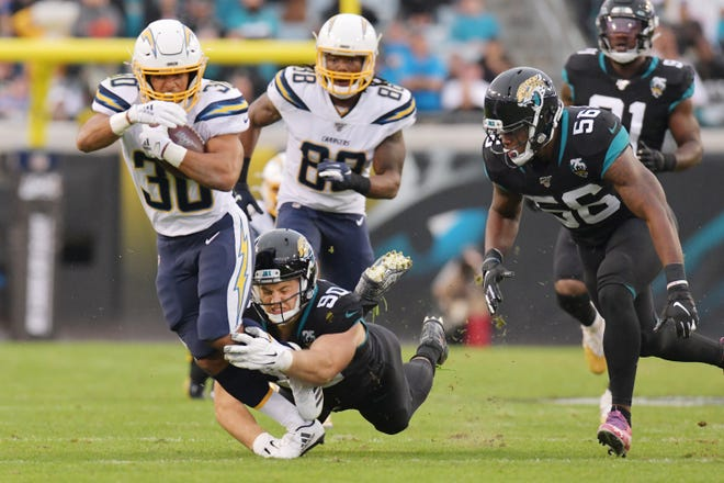 Jacksonville Jaguars defensive tackle Taven Bryan (90) struggles to make a tackle on Los Angeles Chargers running back Austin Ekeler (30) on a 23 yard run midway through the second quarter. The Jacksonville Jaguars hosted the Los Angeles Chargers at TIAA Bank Field in Jacksonville, Florida Sunday, August 10, 2018. The Jaguars trailed at the half 24-3. [Bob Self/Florida Times-Union]
