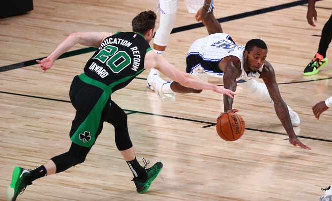 Orlando Magic forward Gary Clark (12) dives for a loose ball against Boston Celtics forward Gordon Hayward (20) during overtime of an NBA game Sunday in Lake Buena Vista. [Kim Klement/The Associated Press]