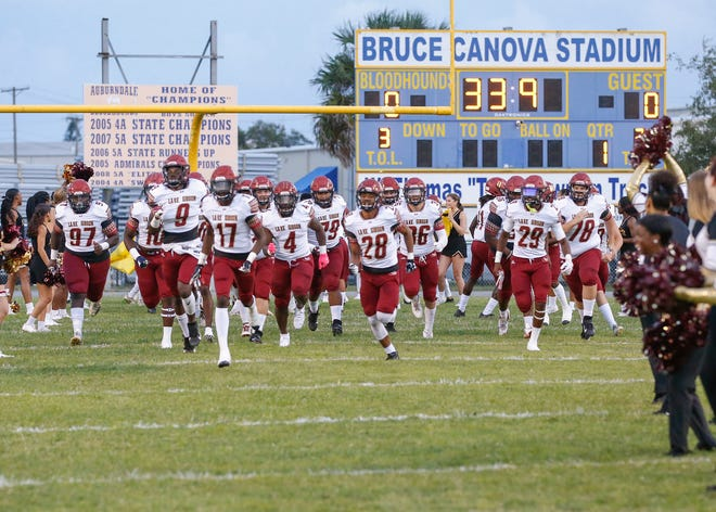 Lake Gibson has shut down summer conditioning workouts because of COVID-19 concerns and will re-evaluate the situation Monday. Above: The Braves run onto the field before a game against Auburndale at Bruce Canova stadium in Auburndale, this past season.    [PIERRE DUCHARME/THE LEDGER]