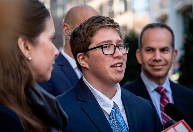 FILE- In this Dec. 5, 2019 file photo, Transgender student Drew Adams speaks with reporters in December 2019 outside of the 11th Circuit Court of Appeals in Atlanta. A federal appeals court said Monday that a Florida school district was wrong when it forced a transgender student to either use a girls or gender neutral bathroom even though he identified as a boy.
