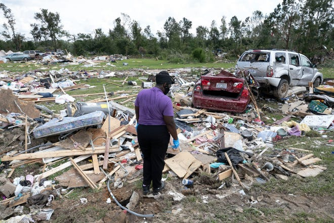 Cynthia Cooper looks for personal items for a family member who had their home destroyed after a tornado spawned by Hurricane Isaias destroyed a rural mobile home neighborhood killing two residents near Windsor, N.C., on Aug. 5. [ROBERT WILLETT/THE NEWS & OBSERVER via AP]