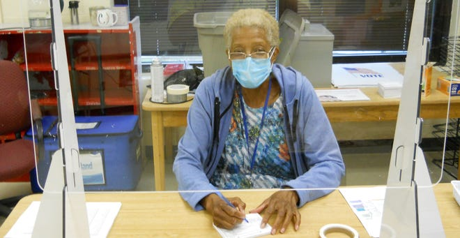 Precinct Manager Delores Cole of the Woodland Precinct in Oak Ridge prepares behind a shield and wearing a mask to register voters.