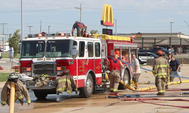 Pratt firefighters roll up and store hoses after putting out a very small fire at Kansas Inn on Aug. 7 after a welder caught wood on fire underneath siding at an outside stairwell.
