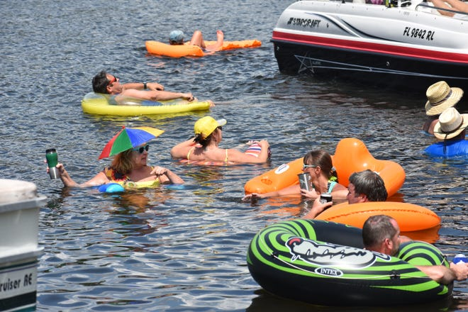 People cool off Thursday before the Milltown Duck Race on the Blackwater River. [FILE PHOTO]