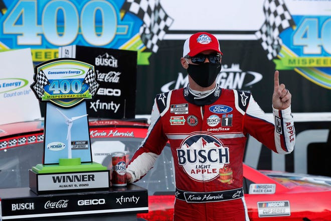 Kevin Harvick celebrates after winning Sunday's NASCAR Cup race at Michigan International Speedway. It gave Harvick back-to-back wins of the weekend's Cup races. [Paul Sancya/The Associated Press]