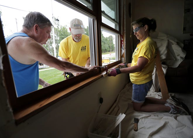 Homeowner Lee Catron, left, helps volunteers Keith Glass and Mary Jo Glass replace a window during a past Rock the Block event in Menasha. Rock the Block will focus on the Columbus Elementary School neighborhood in Appleton in August and September.
