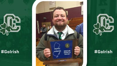 Camden Catholic's Bill Heverly proudly shows off some of the hardware the Irish have earned in recent years. Last week, Heverly was named the program's head coach.