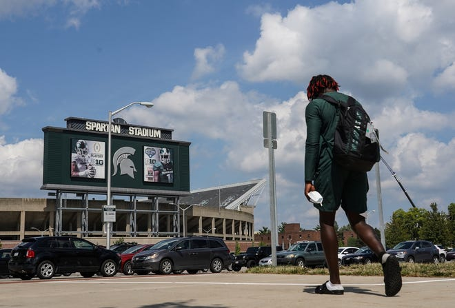 A Michigan State football player walks back to his car at Spartan Stadium following practice on the campus in East Lansing on Monday, August 10, 2020.
