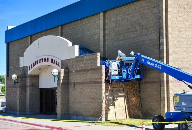 A work crew from MT Elastomers repairs peeling paint on awnings at the entry to the Exhibition Hall by sandblasting and grinding and coating with a tinted elastomer coating that will match the teal-colored trim on the building.  Since COVID-19 canceled the2020 State Fair and postponed a host of other popular events the county is taking advantage of the limited use of the fairgrounds in 2020 to fix up ExpoPark.