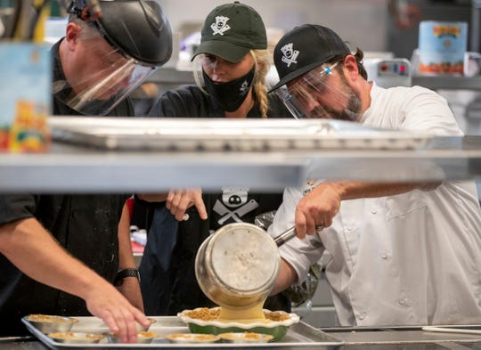 David Lee (left), and fellow sous chef Gannon Cooper help Josh Cooper with his sugar cream pie creation during the filming of World Food Championships, at Ivy Tech Community College, Indianapolis, Sunday, Aug. 9, 2020. This final round of the weekend's competition pits three cooks in a sugar cream pie contest.