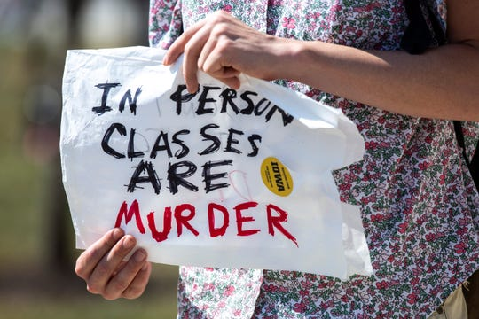 "A persons hold a sign reading, ""In person classes are murder"" during a protest Aug. 10 on the University of Iowa campus in Iowa City, Iowa."