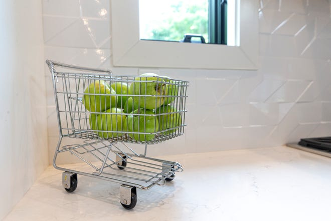 A small grocery cart holds apples on the kitchen counter of David and Pam Biddle's home. Aug. 10, 2020