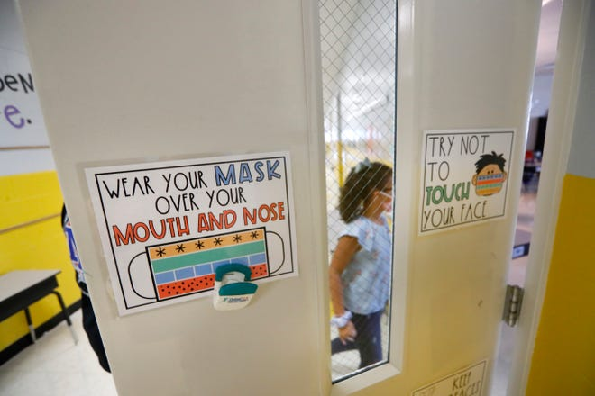 Students return to their classrooms as signage guides proper use of mandated face masks for first and second graders in the hallway at Millington Elementary School on the first day of class Monday, August 10, 2020. Masks will now also be required for students at schools in the Germantown Municipal School District, also in Shelby County.