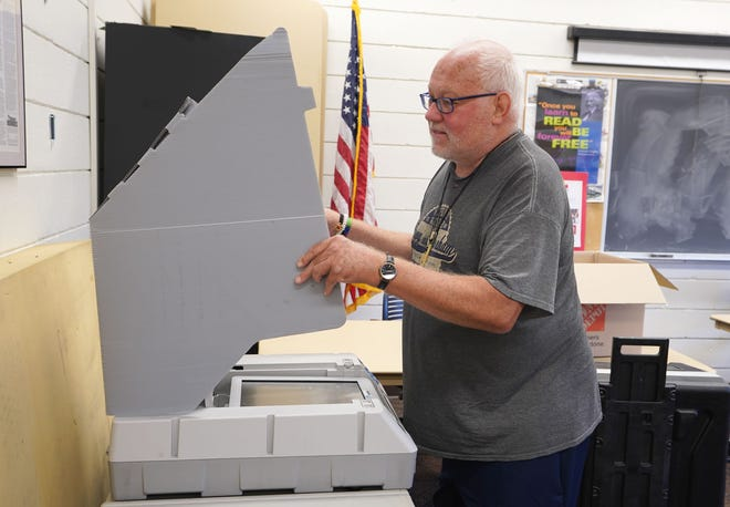 Michael Lisowski , a chief poll worker, sets up a voting booth in preparation for Tuesday's primary election at the Milwaukee Public Library branch on West Atkinson Avenue on Monday, Aug. 10, 2020.