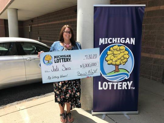 Penduduk St. Clair County Jodi Sass berdiri dengan cek peringatan merayakan kemenangannya dalam permainan instan Millionaire Maker dari Lotere Michigan.