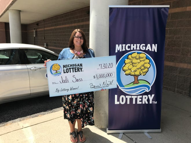 St. Clair County resident Jodi Sass stands with a commemorative check celebrating her win in the Michigan Lottery's Millionaire Maker instant game.
