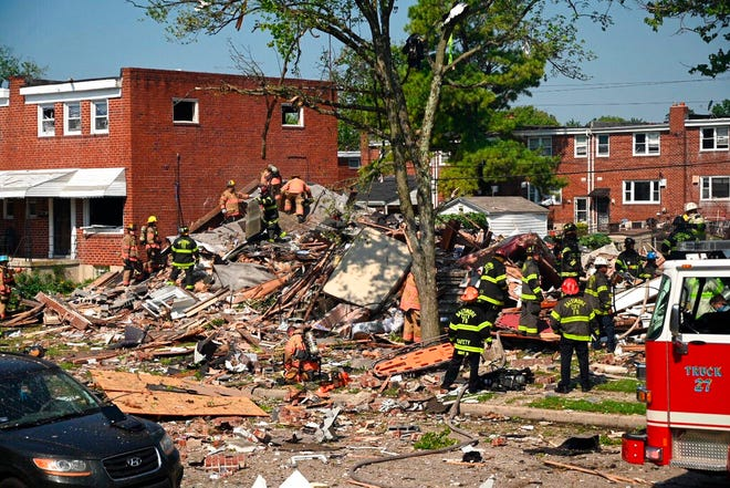 Firefighters at the scene of where homes are destroyed  Monday, August 10, 2020 at Boxhill Road and Reisterstown Road in Northeast Baltimore. A natural gas explosion has completely destroyed three row houses in Baltimore, killing at least one person and critically injuring several others.  (Jerry Jackson/The Baltimore Sun via AP)