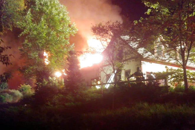In this Sunday, Aug. 9, 2020 photo, a massive fire engulfs the home of cooking show star Rachael Ray, in Lake Luzerne, NY. Ray's representative said in a statement that Ray, her husband and dog were safe, but that the extent of damage to the home was not yet clear. (Courtesy Kenneth Dickinson via AP)