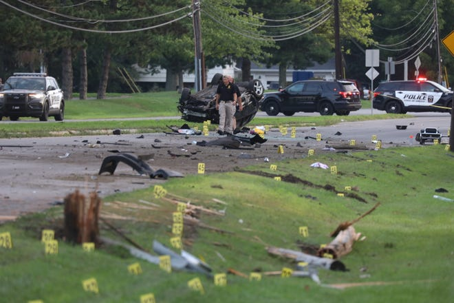 Greece police officers walk through a debris field on Mount Read Boulevard following a one-car crash that killed a driver on Aug. 10, 2020.