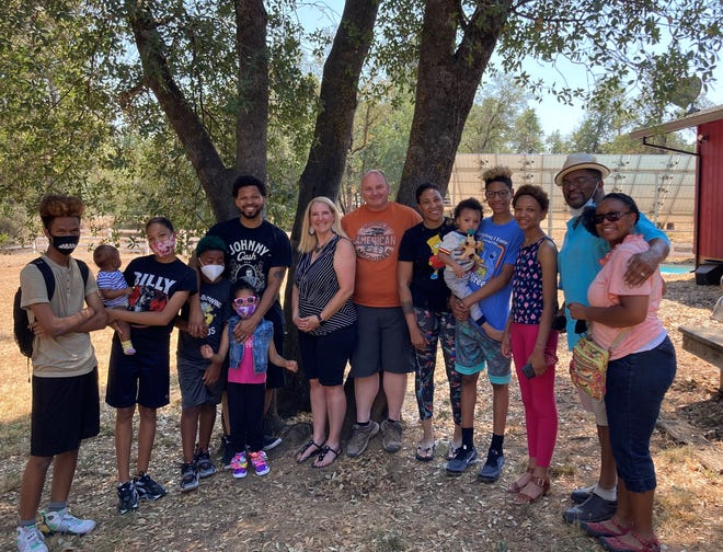 California Highway Patrol Officer Chance Clark, center in orange shirt, offered to let Natasha Manning-Redmond and her family stay at his Redding home after her car broke down on Interstate 5 and she couldn't find a hotel room in the Redding area.