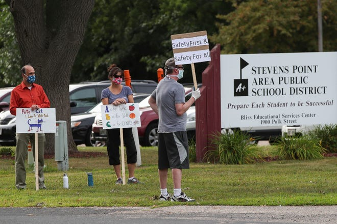 Protesters hold signs in opposition to the Stevens Point Area Public School District's plan to reopen for in-person learning Monday, Aug. 10, 2020, outside the Bliss Educational Services Center, 1900 Polk St., Stevens Point.