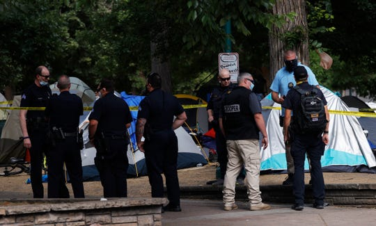 Like many cities across the country, Denver is suffering a wave of gun violence and 38 people have died in suicide by the end of June, putting the city on track to have one of its deadliest years within at least one decade.  In the photo: Denver Police Department officers investigate a shooting between tents set up by homeless people in a park beyond the State Capitol on Thursday, July 23, 2020, in downtown Denver.