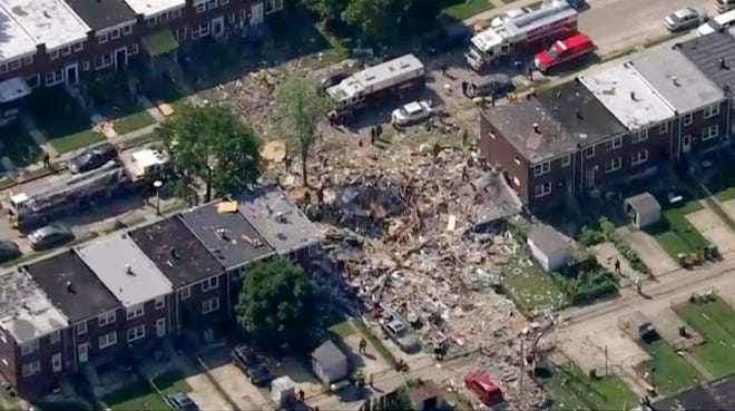 A natural gas explosion destroyed three row houses in Baltimore on Monday, killing a woman and trapping other people in the wreckage.