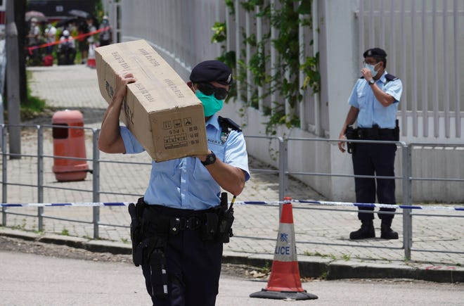 A police officer carries a box of tent before set up outside Apple Daily headquarters as Hong Kong media tycoon Jimmy Lai, who founded local newspaper Apple Daily, is arrested by police officers at his home in Hong Kong, Monday, Aug. 10, 2020. Hong Kong police arrested Lai and raided the publisher's headquarters Monday in the highest-profile use yet of the new national security law Beijing imposed on the city after protests last year.
