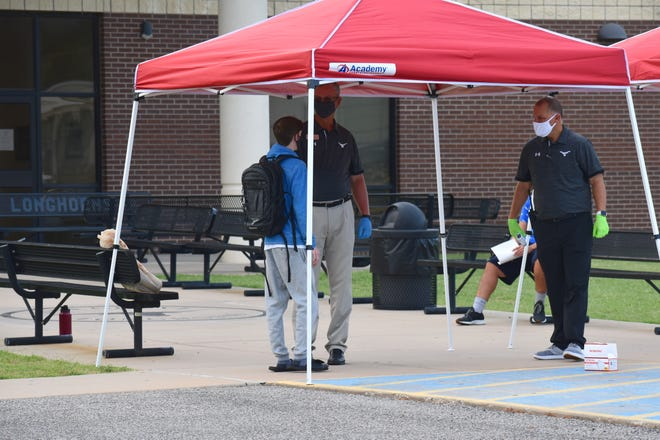 Lone Grove High School Principal Chris Sudderth (far right) and Assistant Principal Derek Hallum speak to a masked student Tuesday morning. Temperature checks before building entry is one of the precautions taken at all Lone Grove campuses.