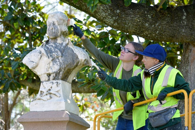 Maddalena Fanconi (left) and Maeve O'Shea from EverGreene Architectural Arts use mild soap and water as they scrub the marble and stone bust of Scottish poet and lyricist Robert Burns erected by the Robert Burns Association of Jacksonville. The work is part of a citywide project to repair and restore some of the city's public art.