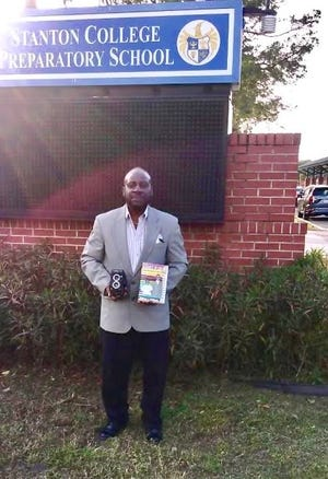 "Michael Williams, a visual arts teacher in Duval County Public Schools for 40 years, stands outside the school where took a class in 1970 that he says changed his life. He's holding the camera the twin-lens reflex camera he learned to use in that class -- and a copy of the book he wrote last year, ""A Choice of Colors: The Inspirations and Struggles of a Duval Colored Teacher."""
