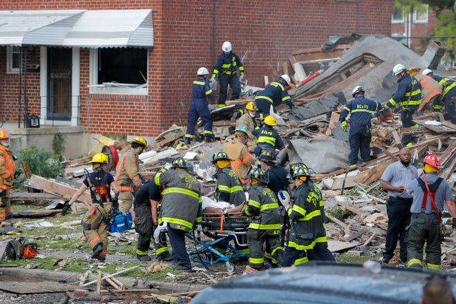 Baltimore City Fire Department carries a person out from the debris after an explosion in Baltimore on Monday. An explosion levelled several homes in the city.