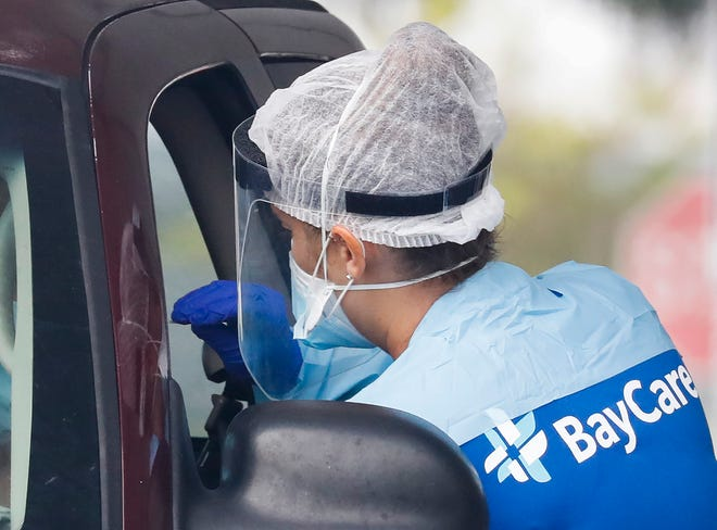 A BayCare COVID-19 testing team member administers a test at the drive-thru facility on the Gil Jones Center campus in Winter Haven on July 31. Winter Haven City Commission extended the city's face mask law Monday to help limit spread of the disease. [PIERRE DUCHARME/THE LEDGER]