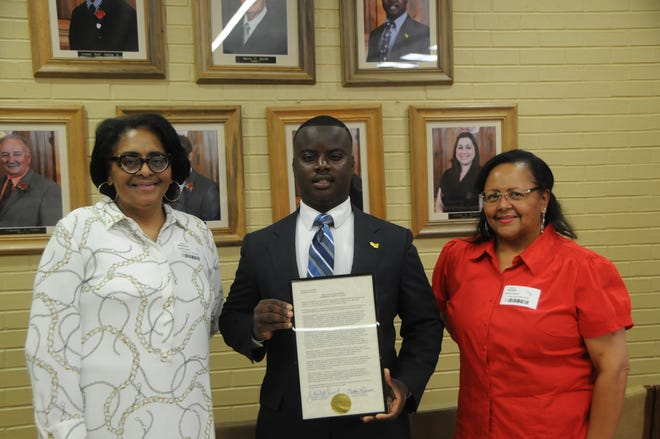 """District 6 Iberville Raheem Pierce presented a plaque in honor of the late Harriet Collins Tillman to her daughters, Carol Tillman Marcelin and Paula Tillman Warner, during the July 21 meeting, which coincided with """"Harriet Collins Tillman Day,"""" as proclaimed by Parish President J. Mitchell Ourso."""