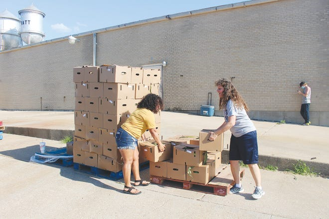 Pratt volunteers Anel Cox and Stephanie Becker load free produce boxes into vehicles at the Pratt Community Center, one of several food distribution points in the past few days in Pratt.