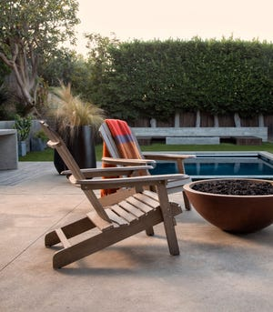 TAKE IT OUTSIDE: Since the pandemic has made the outdoors the preferred gathering place, interest in outdoor furnishings, like the Adirondack chairs and fire pit pictured, has been on the rise, a new study shows. (Photo courtesy of Living Spaces)