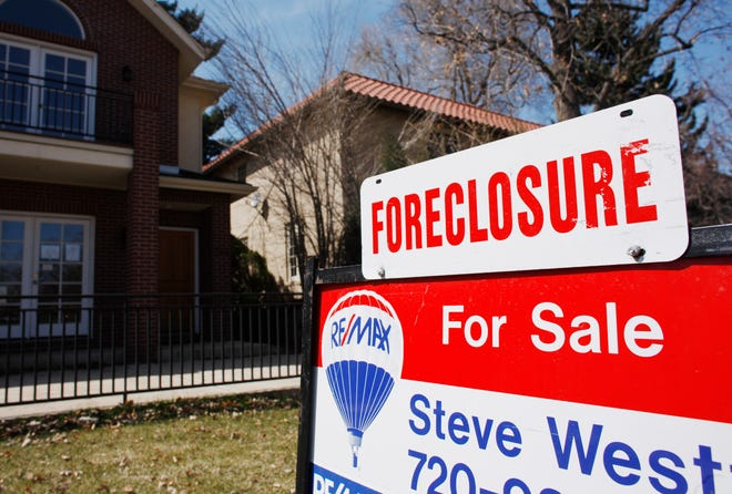 In this April 4, 2010, file photo, a foreclosure sign tops the for sale sign outside a home in Denver. As the coronavirus pandemic continues to undermine the Sarasota-Manatee economy, more homeowners are failing to pay their mortgages on time. [David Zalubowski, AP]