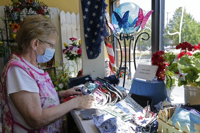 Barbara Ann Elmer, co-owner of Cedar Ridge Crafts & Gifts in Neenah, arranges the masks for sale.