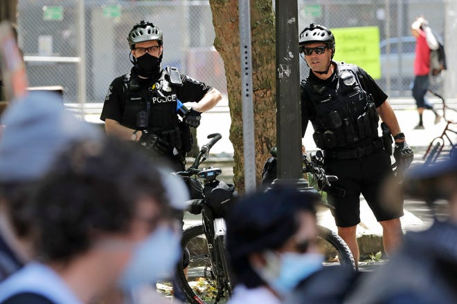 FILE - In this July 20, 2020, file photo, police officers look on at protesters in Seattle.