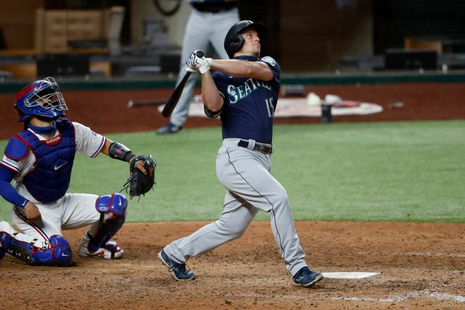 Seattle Mariners' Kyle Seager, right, follows through on a grand slam as Texas Rangers catcher Robinson Chirinos looks on in the sixth inning of a baseball game in Arlington, Texas on Monday. The hit also scored Kyle Lewis, Dylan Moore and J.P. Crawford.