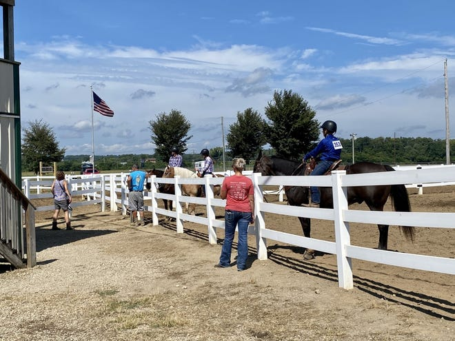 Before competing in the Junior Fair Horse Show, exhibitors wait inside a corral before it's their time to show. Usually, riders take time to talk to each other while waiting but amid social distancing guidelines this year, most opted not to.