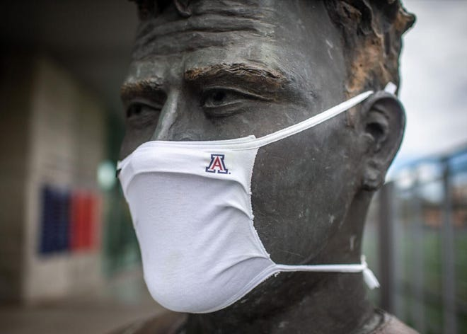 "The John ""Button"" Salmon statue outside Arizona Stadium sports a mask."