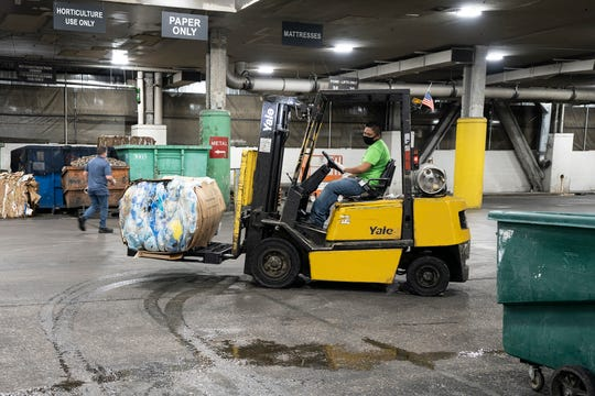 A staff member at the Venetian Resort Las Vegas moves bundled masks which will be recycled to make shipping pallets, composite decking and composite lumber.