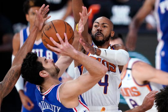 Aug 11, 2020; Lake Buena Vista, Florida, USA;   Philadelphia 76ers guard Furkan Korkmaz, left, takes a shot as Phoenix Suns guard Jevon Carter (4) defends during the first half of an NBA basketball game Tuesday, Aug. 11, 2020, in Lake Buena Vista, Fla.  Mandatory Credit: Ashley Landis/Pool Photo-USA TODAY Sports