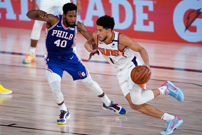 Phoenix Suns guard Devin Booker (1) drives past Philadelphia 76ers forward Glenn Robinson III (40) during the first half of an NBA basketball game Tuesday, Aug. 11, 2020, in Lake Buena Vista, Fla. (AP Photo/Ashley Landis, Pool).
