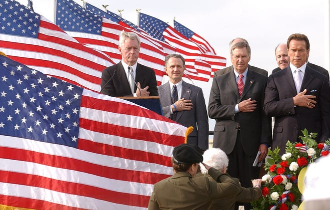 California Gov. Arnold Schwarzenegger, right, takes part in a dedication of the long-awaited Northern California Veterans Cemetery on Veterans Day, Friday, Nov. 11, 2005, near the town of Igo, Calif., 10 miles southwest of Redding. More than 500 people were on hand for the dedication of California's only state-run cemetery. Beside Scwarzenegger are, from left, master of ceremonies Stan Statham, Rep. Wally Herger, R-Calif., and California Secretary of  Veterans Affairs Tom Johnson.