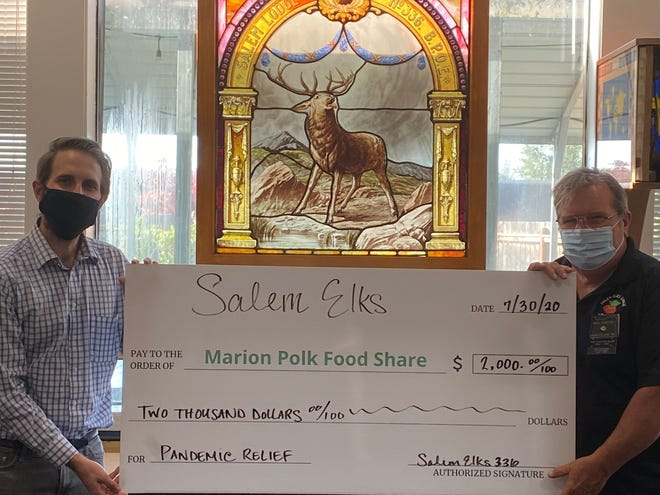 Josh Gwin, right, of Marion Polk Food Share accepts a $2,000 grant donation from Mike Carter of Salem Elks Lodge #336.