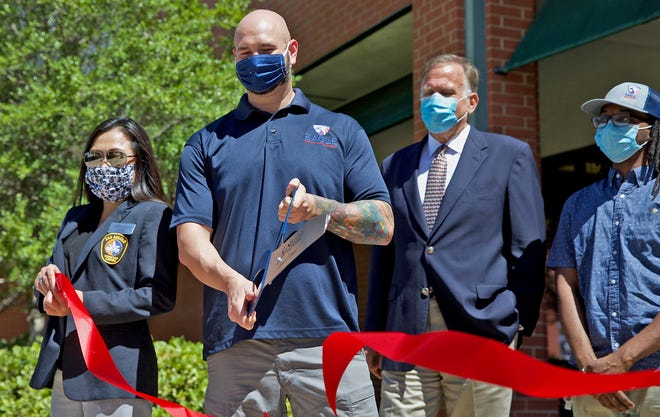 Tommy Anthony, Chief Operations Officer of Eagle Safety Management at center, cuts the ribbon during an event to celebrate the company's new service to combat COVID-19 on Monday, Aug. 10, 2020.