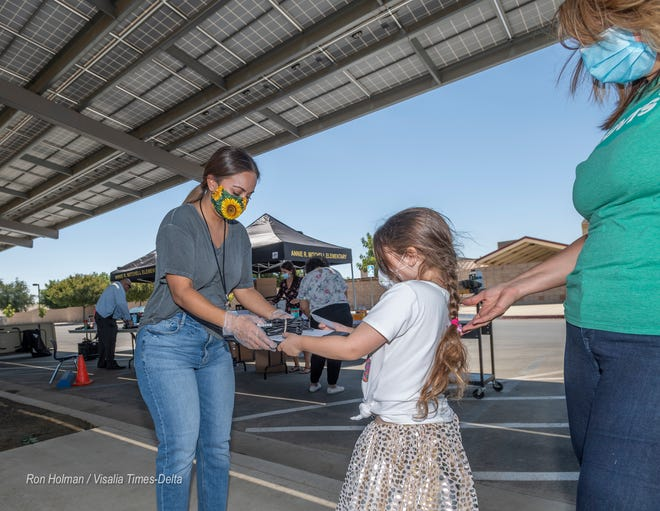 Annie R. Mitchell faculty members hand out Chromebooks to students on Monday, August 10, 2020. The district is beginning the 2020-21 school year with remote learning.