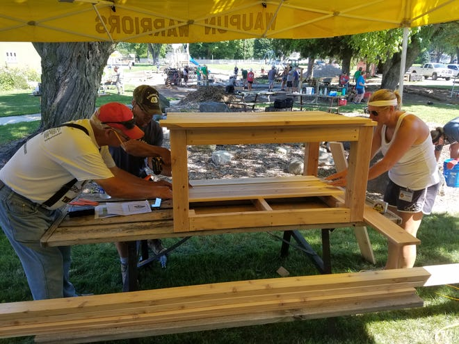 Volunteers Ron Daane and Brian Tenpas, left, work on building a construction table that students will use to build things in their outdoor classroom and play ground. Assisting them is physical education teacher Jackie Clark.